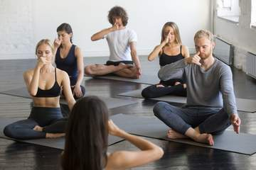 Group of young sporty people practicing yoga lesson with instructor, making nadi shodhana pranayama exercise sitting in Sukhasana pose, friends working out in gym, studio. Wellbeing, wellness concept